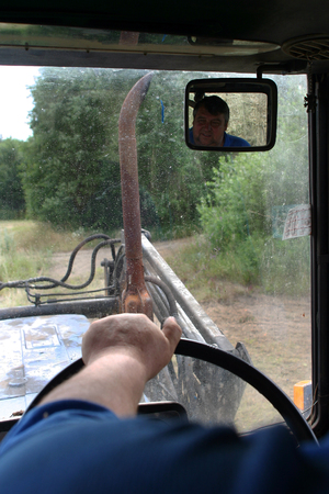 peasant farming: Lemozero, Olonets, Karelia, Russia - July 26, 2006: Closeup of  hand tractor driver on tractor steering wheel, in rearview mirror face of driver is reflected.