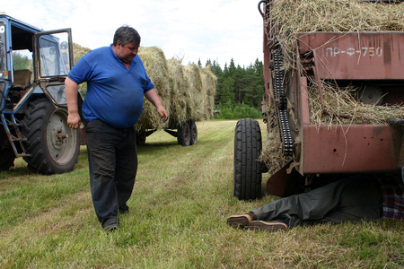 baler: Lemozero, Olonets, Karelia, Russia - July 26, 2006: Farmer repairing round baler, in field, during hay.