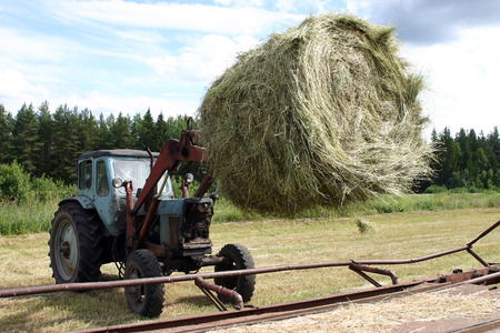 tipping: Lemozero, Olonets, Karelia, Russia - July 26, 2006: Tractor with bucket fork carries a round bale of hay in Cereal tipping trailer.
