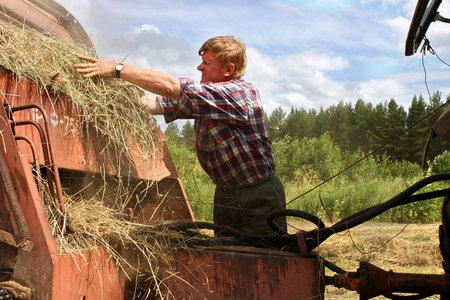 baler: Lemozero, Olonets, Karelia, Russia - July 26, 2006: Hay harvest, tractor harvesting hay baler, farmer repair Used farm equipment.
