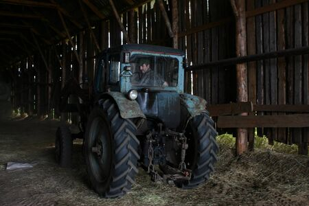 agriculturalist: Lemozero, Olonets, Karelia, Russia - July 26, 2006: Blue farm tractor, with the driver of the tractor, parked in a wooden barn for hay. Editorial