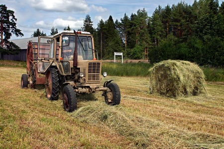 haymaking: Lemozero, Olonets, Karelia, Russia - July 26, 2006: Harvest of hay on the Russian fields, farm Tractor pulls Round Baler whilst Haymaking. Editorial