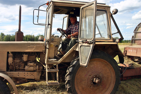 peasant farming: Lemozero, Olonets, Karelia, Russia - July 26, 2006: Tractor cab with door open, farmer tractor driver working on haymaking.
