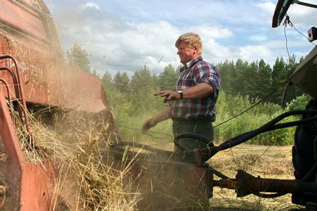 farm equipment: Lemozero, Olonets, Karelia, Russia - July 26, 2006: Hay harvest, tractor harvesting hay baler, farmer repair Used farm equipment.