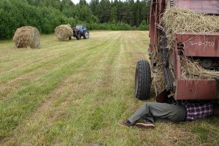 baler: Lemozero, Olonets, Karelia, Russia - July 26, 2006: Peasant Farmer repairing round baler, in field, during make hay. Editorial