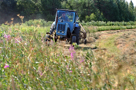 agriculturalist: Lemozero, Olonets, Karelia, Russia - July 26, 2006: Farming tractor working in field of freshly cut during hayfield.