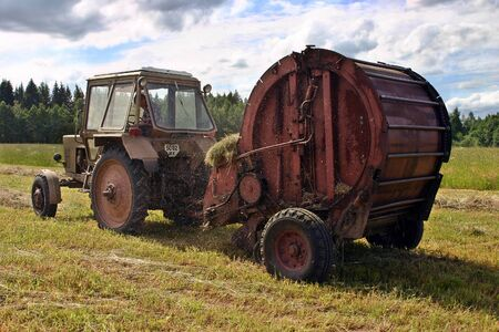 baler: Lemozero, Olonets, Karelia, Russia - July 26, 2006: Harvest hay in Russian north, Circular hay baler and farm tractor, on hayfield. Editorial