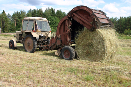 baler: Lemozero, Olonets, Karelia, Russia - July 26, 2006: Russian farmland, time to haymaking, farmers wheeled tractor with round baler for collecting hay.