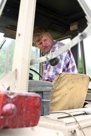 peasant farming: Lemozero, Olonets, Karelia, Russia - July 26, 2006: Farmer tractor driver sits in a cab and looks back. Editorial