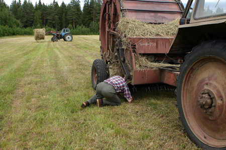 agriculturalist: Lemozero, Olonets, Karelia, Russia - July 26, 2006: Farmer tractor driver mechanic repairing round baler, in field, during make hay.