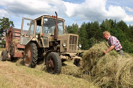 baler: Lemozero, Olonets, Karelia, Russia - July 26, 2006: Russian farmer tractor driver working in the field, he is spreading the dry grass in front of a tractor with a round baler during harvesting hay. Editorial