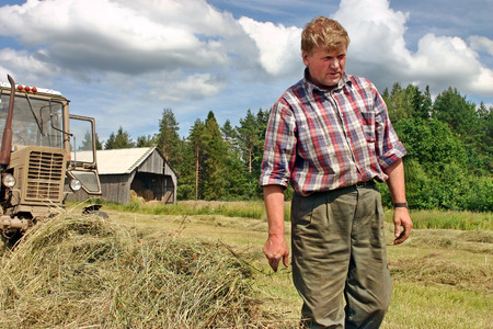 baler: Lemozero, Olonets, Karelia, Russia - July 26, 2006: Harvesting hay in the Russian north, the farmer tractor-driver inspecting the field before the start of hay baler.