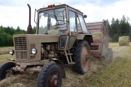 baler: Lemozero, Olonets, Karelia, Russia - July 26, 2006: Farm tractor pulling a baler for harvesting hay.