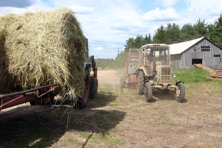 baler: Karelia, Russia - July 26, 2006: Agricultural machinery Russian farmers, tractor hitched to him hay baler and tractor with trailer carrying bales of hay on background of wooden barn, sunny summer day.
