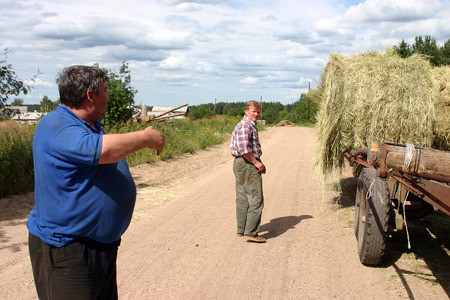 peasant farming: Lemozero, Olonets, Karelia, Russia - July 26, 2006: Farmers discussed haymaking standing next to a trailer loaded with round bales of hay. Editorial