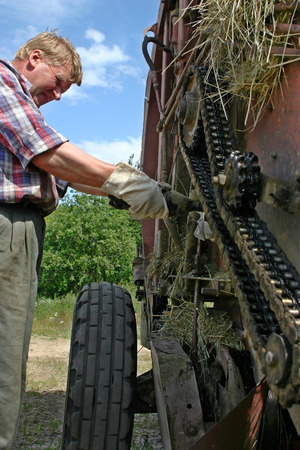 agriculturalist: Lemozero, Olonets, Karelia, Russia - July 26, 2006: Farmer equipment mechanic lubricates the machine oil roller chain mechanism hay baler. Editorial