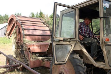 Lemozero, Olonets, Karelia, Russia - July 26, 2006: Countryman farmer cat-skinner, who sitting tractor cabin, with hitched to it round baler dumping a freshly rolled hay bale. Editorial