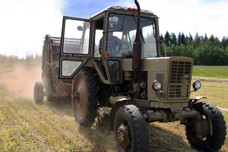 agriculturalist: Lemozero, Olonets, Karelia, Russia - July 26, 2006: Farm tractor wheel with round hay baler on Harvesting Hay In The Field, russian farmland.