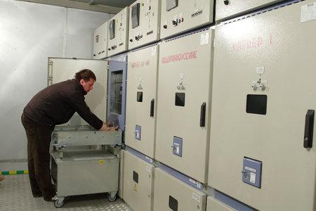 ingeniero electrico: Kirovsk, región de Murmansk, Rusia - 4 de septiembre de 2007: con revestimiento metálico de alta tensión sala de cuadro de distribución, ingeniero eléctrico hacen mantenimiento de la planta minera cuadro eléctrico.