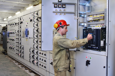 Veliky Novgorod, Russia - June 26, 2007:  Service for high voltage switchgear, electrical engineer maintenance switchboard room,  chemical Plant.