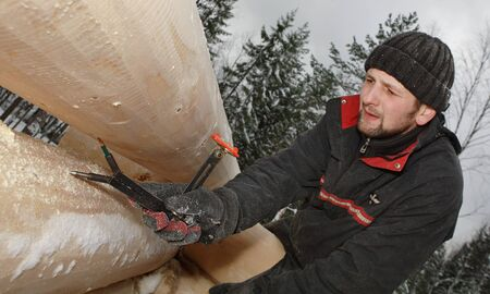 log house: Leningrad region, Russia - February 2, 2010: Carpenter uses a measuring tool during construction log house in the winter woods.