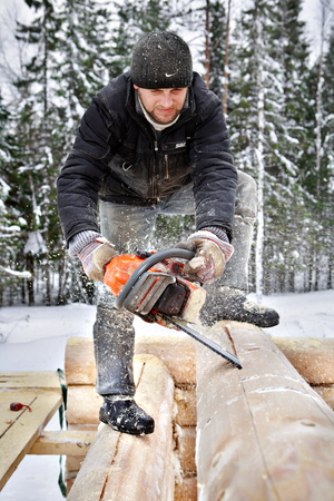 wood craft: Leningrad region, Russia - February 2, 2010: Construction worker builds wooden blockhouse from logs, using a chainsaw. Editorial