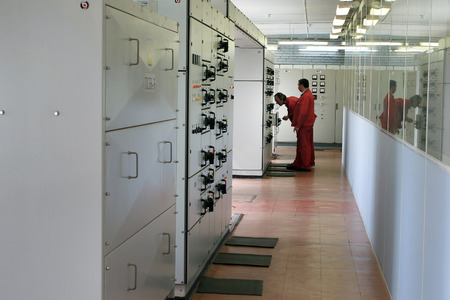 ingenieria elÉctrica: Ciudad Kommunar, región de Leningrado, Rusia - 6 de junio de 2007: Cartón de fábrica, ingeniero inspecciona el cuadro de distribución eléctrica, distribución de habitaciones tablero eléctrico.