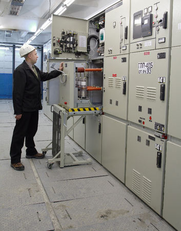 ingenieria elÉctrica: Kovdor, región de Murmansk, Rusia - 3 de septiembre de 2007: Mantenimiento sala de cuadro de distribución de la planta minera, ingeniero eléctrico inspecciona los equipos de distribución de energía eléctrica.