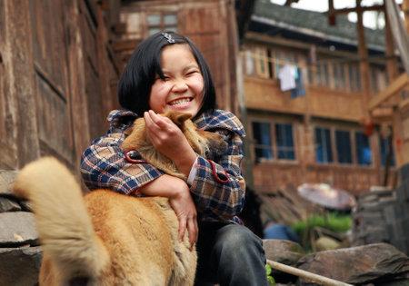 8 years: Guangxi, China -  April 3, 2010: Unknown Chinese girl about 8 years old, hugging light brown dog, village Dazhai, near Longsheng.