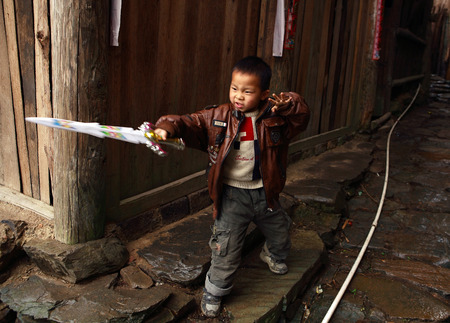 mountainous: GUANGXI PROVINCE, CHINA - APRIL 4: Chinese boy 6 years old, playing with plastic sword near wooden house in village Xiaozhai,  April 4 2010. Village is in mountainous area near Guilin and Longsheng. Editorial