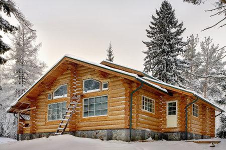 Moderna casa di tronchi a mano con grandi finestre coperte di neve durante l'inverno.