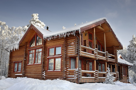 Log cabin with large windows, balcony and porch, modern house design, snowy winter, sunny day. Editorial