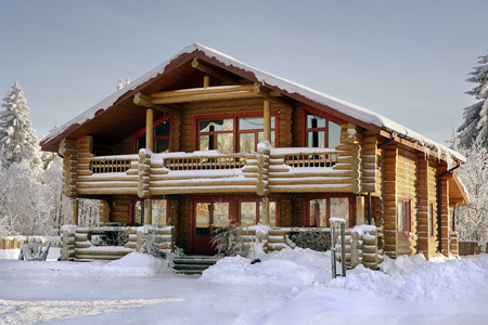 winter vacation: Modern log cabin, wooden vacation home, winter timber house with large windows, balcony and porch, snow-covered spruce forest.