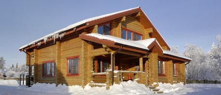 Landhaus, Blockhaus aus gebeiztem Holz hellbraun Schatten, Dach des Hauses ist mit Schnee, sonnigen Wintertag bedeckt.