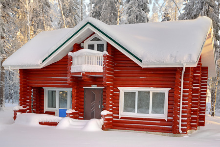 calibrated: Wooden cottage of red painted logs, with snow-covered roof on background of snowy winter forest in daytime.