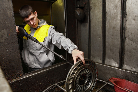 St. Petersburg, Russia - December 23, 2011: Service station, repair shop engine, a young auto mechanic cleans clutch disc, pressure washer.