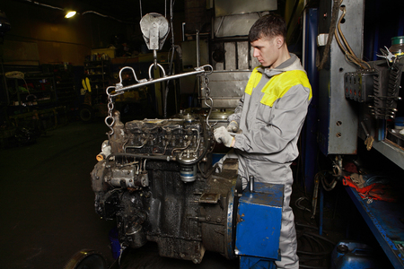 St. Petersburg, Russia - December 23, 2011: Major repairs Motor in auto repair shop auto service stations, a young worker picked up a car engine using a crane. Editorial