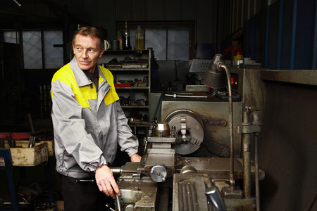 turner: St. Petersburg, Russia - December 23, 2011: Elderly turner turned parts using an outdated lathe turning shop maintenance station forklifts. Editorial