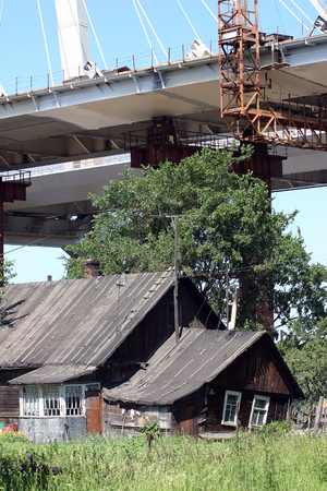 undone: Novosaratovka Village, St. Petersburg, Russia - July 2, 2006: Construction of the cable-stayed bridge over the residential farmhouse in the Russian village.