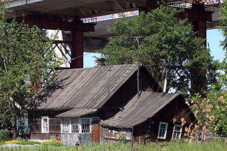 undone: Novosaratovka Village, St. Petersburg, Russia - July 2, 2006: Big cable-stayed bridge under construction over the residential wooden house a sunny summer day.