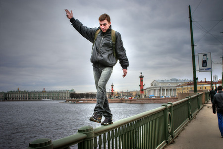 intrepid: St. Petersburg, Russia - April 22, 2006: Young man is walking on thin parapet high bridge. Editorial