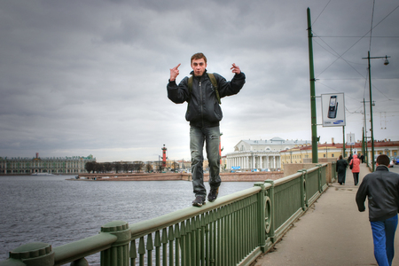 urbanite: St. Petersburg, Russia - April 22, 2006: Man makes risky walk on parapet a bridge and shows passers obscene gesture. Editorial