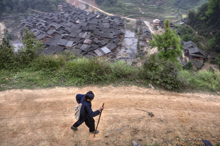field work: Zengchong Dong Village, Guizhou Province, China - April 11, 2010: An elderly Chinese woman walking back from field work, she goes on a mountain dirt road.