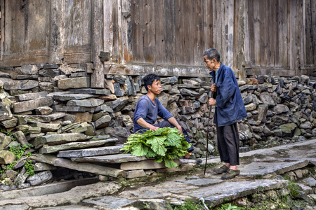 confab: Zengchong Dong Village, Guizhou Province, China - April 11, 2010: Elderly and young farmers talking near wooden barn on a rural street.