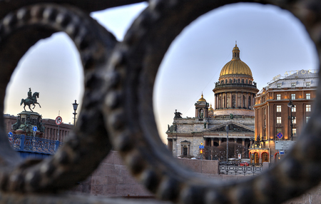 embankment: St. Petersburg, Russia - December 27, 2015: View on St. Isaacs Square and St. Isaacs Cathedral in Saint Petersburg, through the iron fence Moika Embankment.