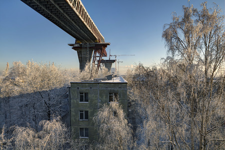 two level house: St.Petersburg, Russia - January 23, 2016: Flyover under construction motor bridge passes over roof an apartment house, Kanonersky island, Saint Petersburg, build overpass road bridge across Sea Canal Editorial