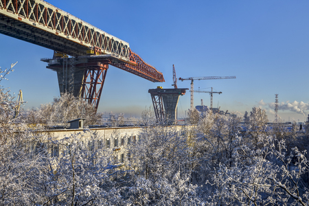 two level house: St.Petersburg, Russia - January 23, 2016: Multiband highway created in dense urban development, residential and industrial areas, Construction road bridge across sea channel, Kanonersky island, winter