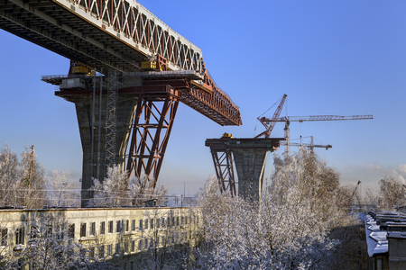 gat: St.Petersburg, Russia - January 23, 2016: Two-level highway bridge flyover through Sea Canal under construction, residential area Kanonersky island, winter day, Saint-Petersburg.