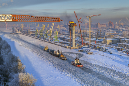 gat: St.Petersburg, Russia - January 23, 2016: Construction of motorway bridge overpass through Sea Canal, the commercial port of Saint Petersburg, winter.
