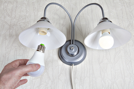 Replacing the electric light bulbs in a household wall lamp, LED light bulb in human hand, close-up.